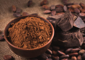 Cocoa beans, clay bowl with cocoa powder, black chocolate on brown sacking