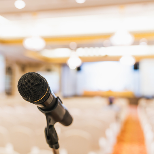 Microphone stand in conference hall blurred background with copy space. Public announcement event, Organization company meeting, live performance media, or graduation education award ceremony concept