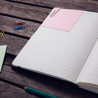 Close-up of diary, sticky notes, pencil and paper clip on wooden table